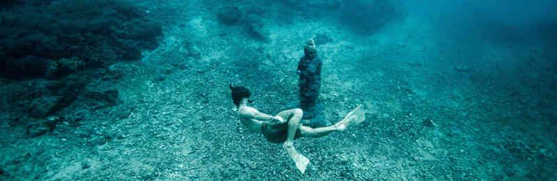 Taucher vor einer Statue auf dem Meeresgrund